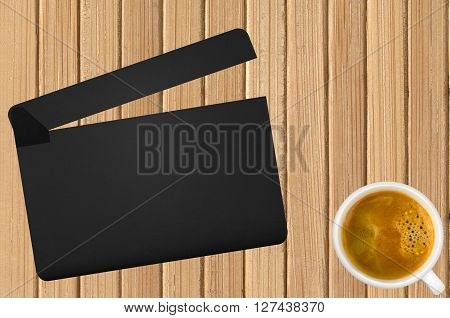 Movie clapper and coffee cup on wooden background