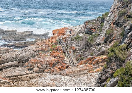 STORMS RIVER MOUTH SOUTH AFRICA - MARCH 1 2016: Unidentified hikers on the staircase at Guano Cave on the Waterfall trail which also is part of the renowned Otter trail