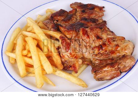 Chicken meat with french fries on white plate