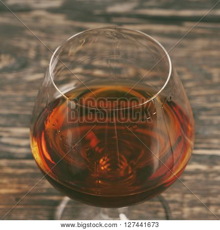 Cognac brandy or whiskey in large round glass on the old wooden table closeup top view