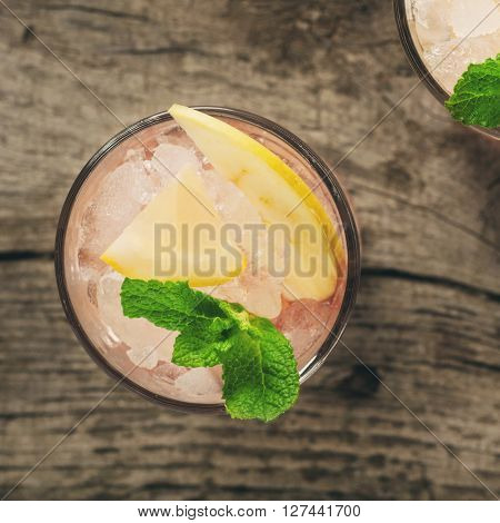Summer cocktail with ice lemon apple and mint on dark wooden background top view