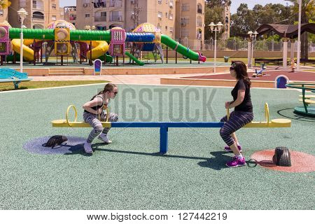 mother and daughter ride on a swing at the city playground