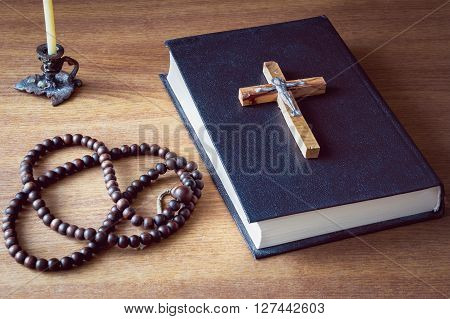 Holy bible, cross and old rosary on wooden background