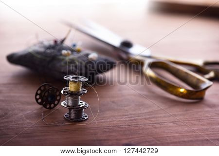 Old sewing machine bobbins,  with gold ( brass ) scissors and pin cushion on a old grungy work table. Tailor's work table. textile or fine cloth making.Shallow depth of field.