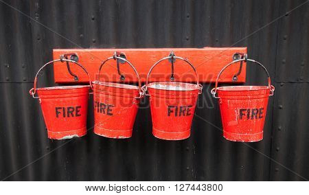 Four vintage battered red fire buckets hanging on hooks against corrugated iron wall