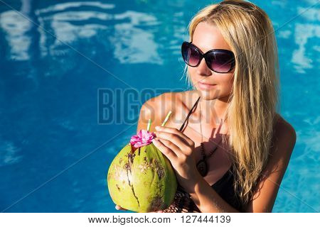Young Pretty Blonde Woman In Swimming Pool With Coconut Coctail Drink