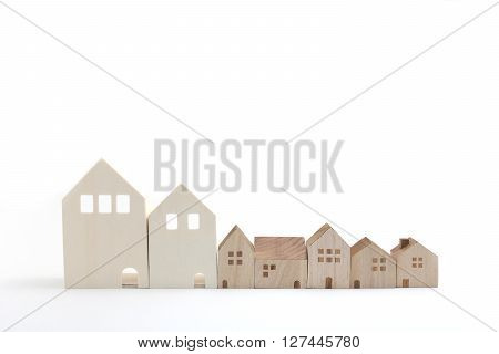 Miniature houses on white background. Building blocks arranged in row.