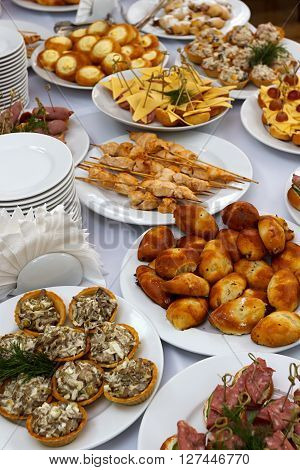 Selective focus photo catering banquet table with baked food snacks sandwiches cakes cups and plates self serve open buffet dinner close up
