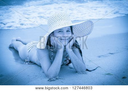 Smiling girl in pink hat on the beach lying down on the sand near water, blue toned picture