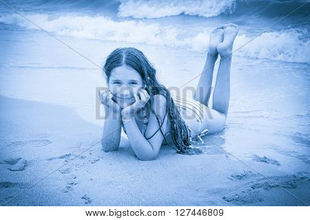 Smiling girl on the beach lying down on the sand near water, blue toned picture