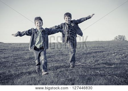 Two happy boys running together on hill with hands as wings, sepia toned
