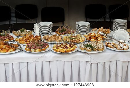 Catering banquet table with baked food snacks sandwiches cakes cups and plates self serve open buffet dinner horizontal view