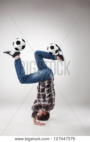 Portrait  of young man, practicing yoga with football balls on gray background. concept of continuous soccer practice