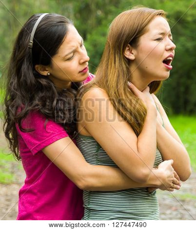Young woman choking with lady standing behind performing heimlich maneuver, park environment and casual clothes.