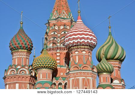 Domes of St. Basil's Cathedral on red square in Moscow. The dome of the Cathedral lit by the sun against the blue sky.