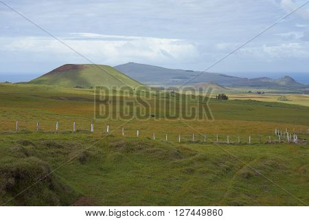 Landscape of Easter Island. Rolling green pasture dotted with the remains of extinct volcanoes.
