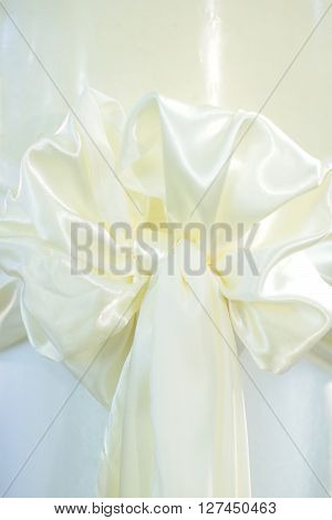 Beautiful bow white silk ribbon festive decorative ornamental knot with tail on whiten background