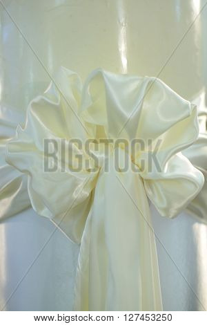 Beautiful bow festive decorative ornamental knot with tail made of white silk ribbon on whiten background