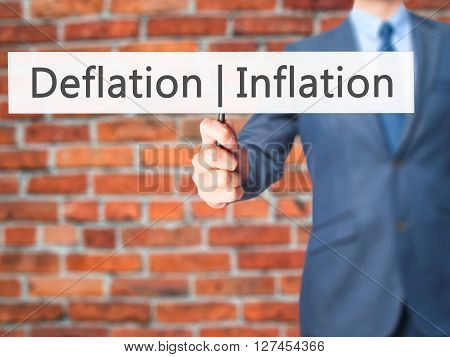 Deflation Inflation - Businessman Hand Holding Sign