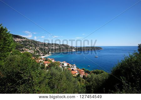 houses villas with terracotta tiled roofs and yachts vessels offshore seacoast of beautiful blue sea on mountain scene