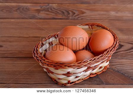 Chicken eggs in a basket. Set the raw chicken eggs. Wooden table
