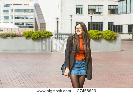 Beautiful Chinese woman walking in London on a sunny spring day. She is wearing smart casual clothes with a denim skirt and eyeglasses. She is smiling and looking away from camera