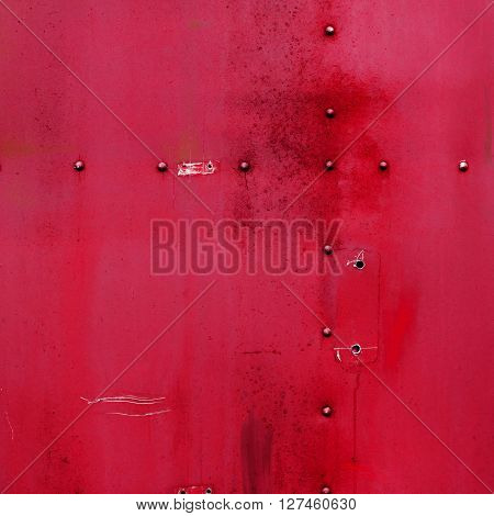 Riveted red metal. Abstract painted matte red metal background texture with rivets. Red metal background