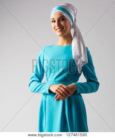 Muslim woman in blue dress on grey