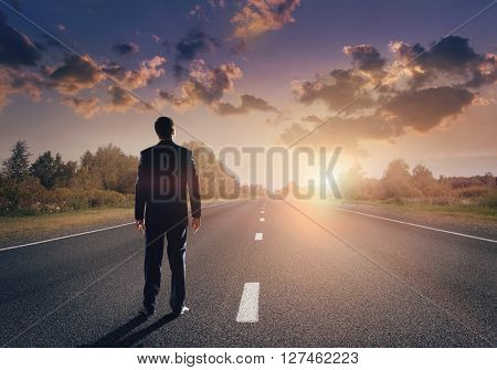 Businessman goes straight on his way on asphalt road ** Note: Soft Focus at 100%, best at smaller sizes