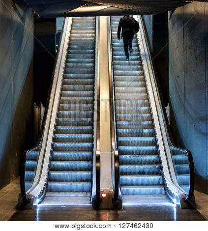 Man ascending an escalator from a subway riding up the moving treads towards daylight at the top view from the bottom