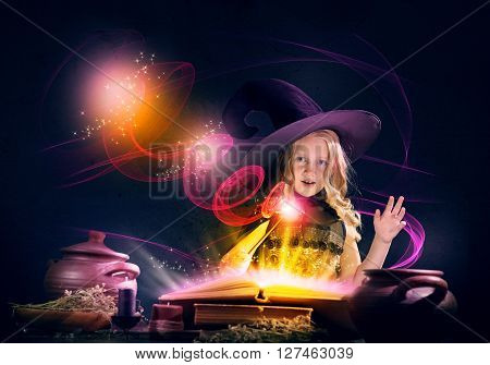 Little Halloween witch reading conjure from magic book above pot