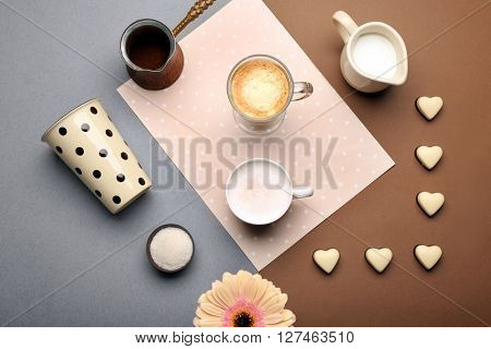 Delicious coffee and milk with candies on table, top view