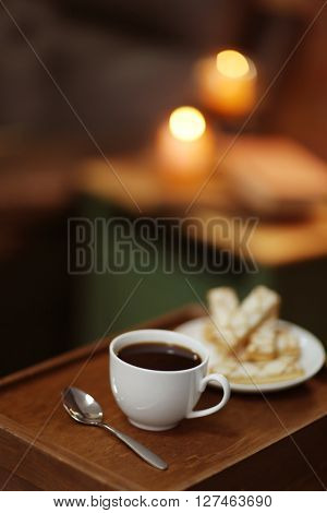 White cup of the coffee and biscuits on a wooden table in a dark room..