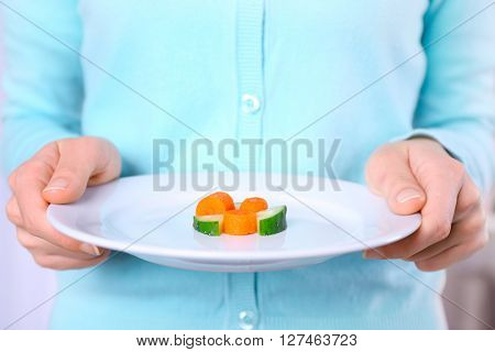 Female hands holding a plate with carrot and cucumber slices.