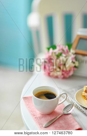 Cup of coffee with cookies on white table in light interior
