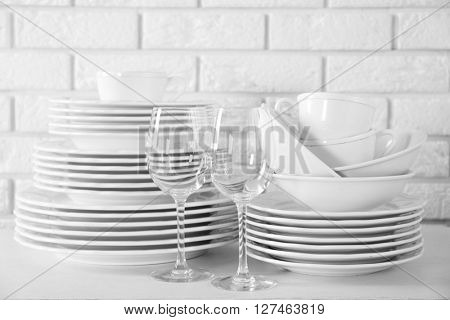 Stacked white clean plates, glasses and cups on  white table