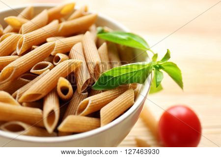 Dry brown penne pasta in white bowl, close up