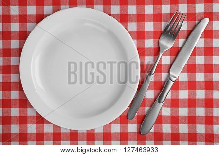 Empty plate with silver cutlery on red checkered background