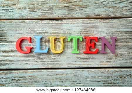 Word GLUTEN made of colorful letters on wooden background