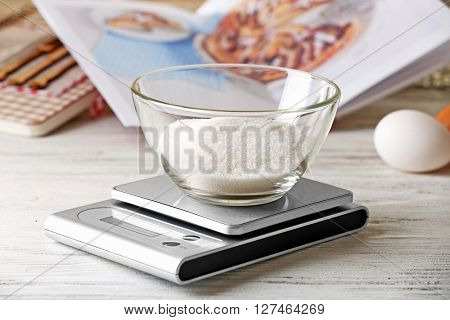 Glass bowl of sugar and digital kitchen scales on light wooden table