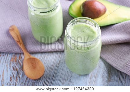 Avocado smoothie on wooden table with napkin closeup