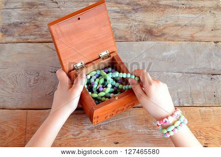 Girl wears bracelets. Children hands take bracelet in wooden box. Old wooden background