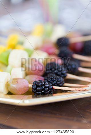 Fresh fruits on a toothpick on a plate