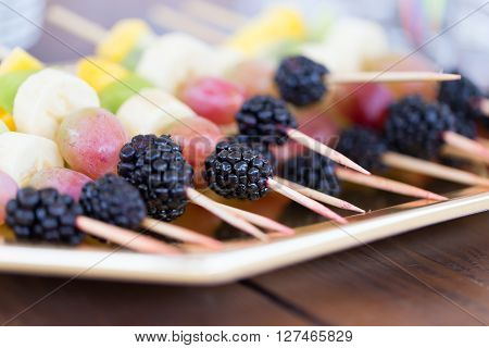 Fresh fruits on a toothpick on a plate