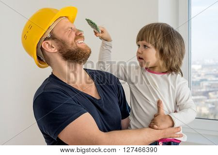 happy family, construction worker in helmet and small child with paint brush