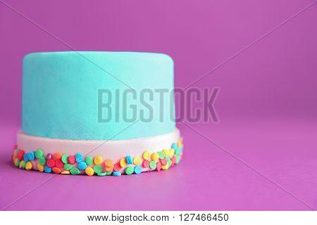 Birthday cake with sprinkles on purple background.