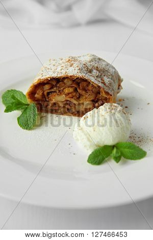 Slice of strudel with apples, walnut, raisins and ice cream ball on white plate