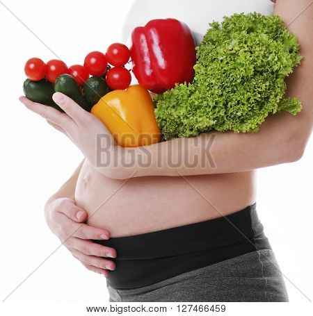 Pregnant woman holding fresh vegetables, isolated on white