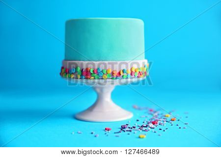 Birthday cake with sprinkles on blue background.