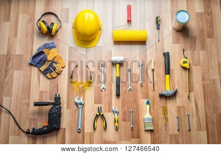 helmet, drill, hammer, work gloves and construction tools on a background of the laminate